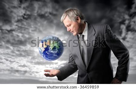 senior businessman taking care of planet earth against a stormy sky