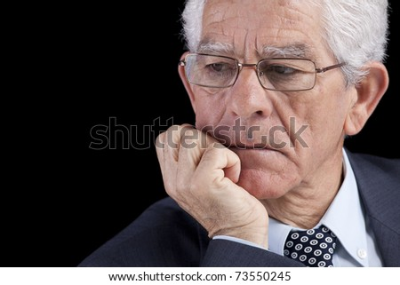 Senior businessman thinking with his hand at the chin (isolated on black)