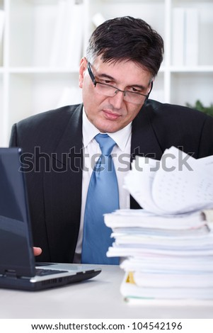 Senior businessman transferring data to the computer, working in office