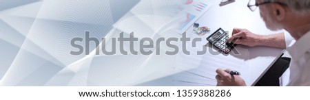 Senior businessman using a calculator in office, hard light. panoramic banner #1359388286