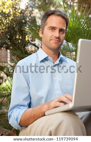 Senior businessman using a laptop computer while sitting on a bench in a city park, outdoors.