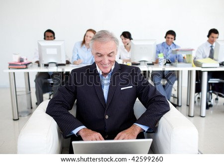 Senior businessman using a laptop with his team in the background