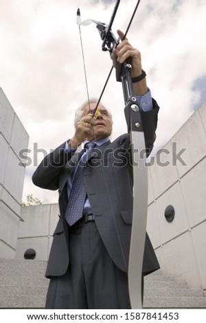 Senior businessman using bow and arrow