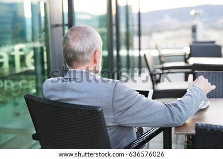 Senior businessman with a tablet in rooftop cafe #636576026