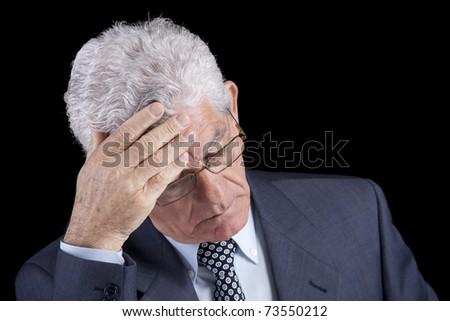 Senior businessman with an headache (isolated on black)
