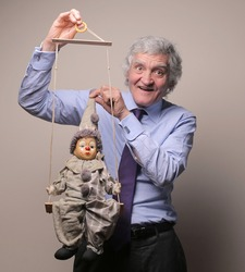 senior businessman with marionette in his hands