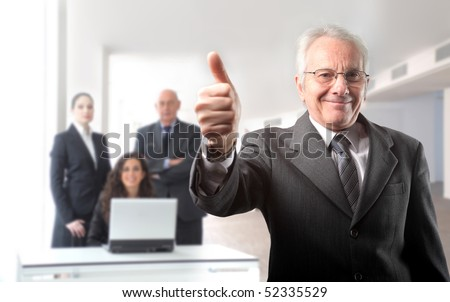 Senior businessman with thumbs up and group of business on the background