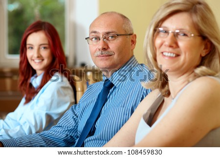 Senior businessman with two female colleagues, all looking to camera