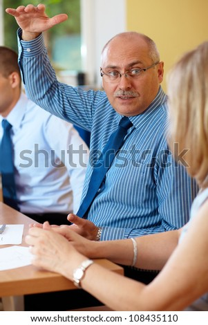 Senior businessman with young colleagues, try to explain and show something