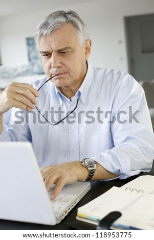 Senior businessman working from home on laptop