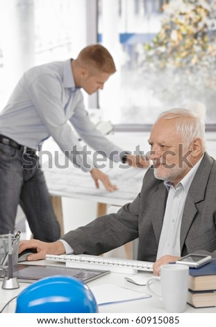 Senior businessman working on computer sitting at table, young architect standing at drawing board in background.?