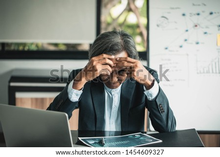 Senior businessmen are worried about the work and the economic downturn. Tired and worried business man at workplace in office holding his head on hands.