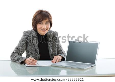Senior businesswoman doing presentation, sitting at desk using laptop computer. Copy space on blank screen.