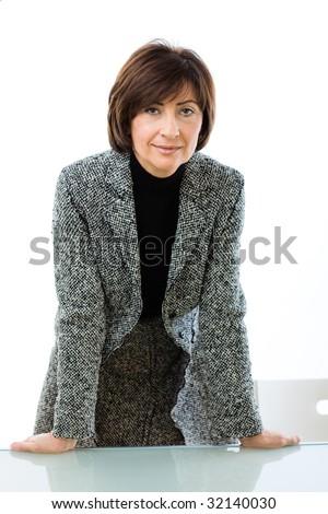 Senior businesswoman leaning on glass desk, smiling.
