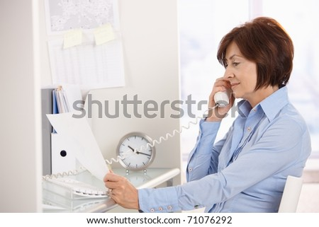 Senior businesswoman listening to landline phone call reading paper handheld.?