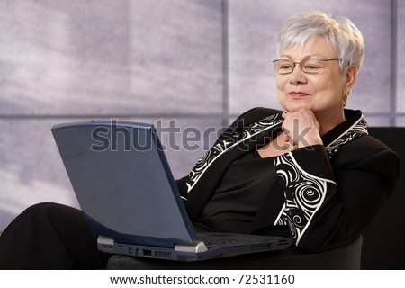 Senior businesswoman sitting in office armchair, using laptop computer, smiling.?