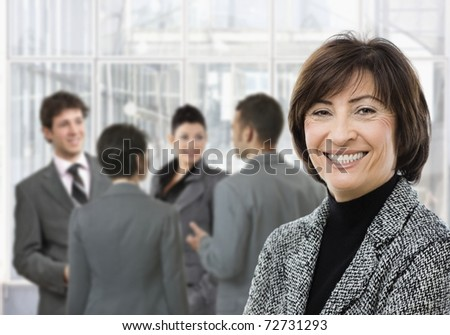 Senior businesswoman smiling, looking at camera, businesspeople in conversation in lobby.?