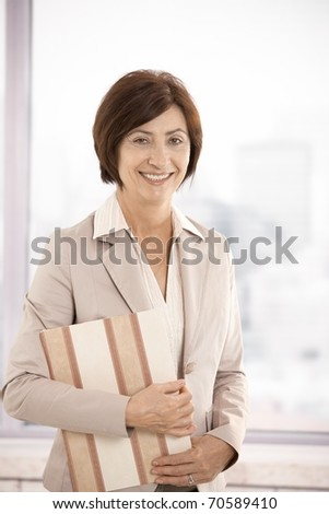 Senior businesswoman smiling, standing in office, holding folder in arm, looking at camera.?