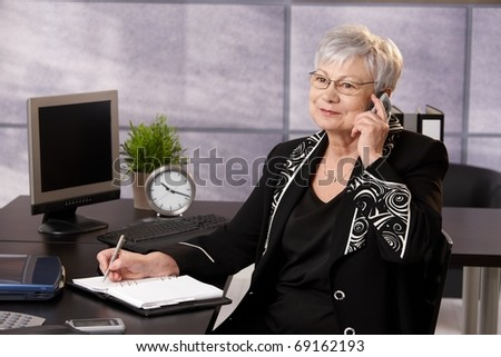 Senior businesswoman using cellphone at desk, taking notes, smiling.?