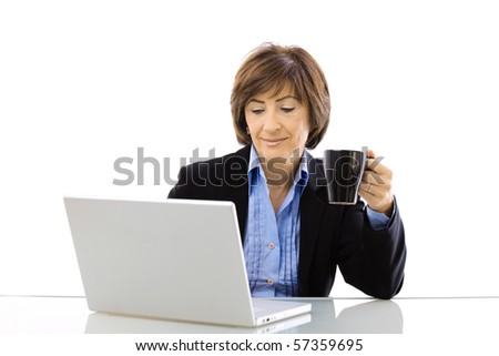 Senior businesswoman using laptop computer while drinking coffee, looking at screen and smiling. Isolated on white background.