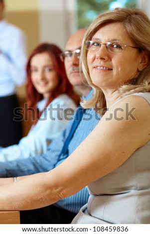 Senior businesswoman with two colleagues sitting at conference table
