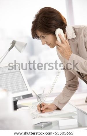 Senior businesswoman working in office, standing at desk, talking on landline phone, taking notes.