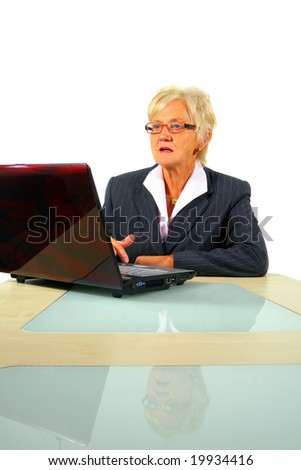 Senior Businesswoman Working On Laptop A senior businesswoman in her fitifties is working on a laptopt in an office.The table mirrors the image creating a nice effect! Isolated over white.