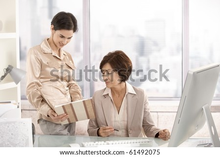 Senior businesswoman working with assistant in office.?
