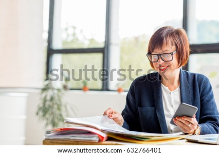 Senior businesswoman working with documents and smartphone at the bright modern office interior stock photo