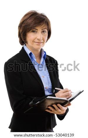 Senior businesswoman writing to notebook, smiling and looking at camera. Isolated on white background.