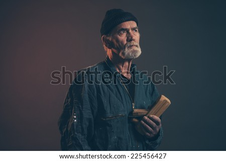 Senior carpenter with gray hair and beard holding old plane wearing black hat with green overalls. Low key studio shot.