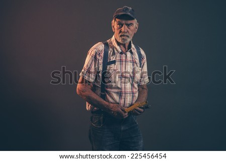 Senior carpenter with gray hair and beard holding yellow measuring rod wearing blue cap with braces and jeans. Low key studio shot.