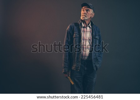 Senior carpenter with gray hair and beard holding yellow measuring rod wearing blue cap with jeans jacket. Low key studio shot.