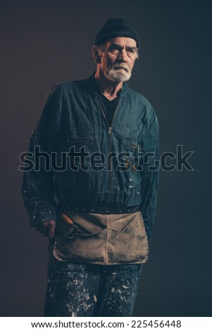Senior carpenter with gray hair and beard wearing black hat with green overalls. Low key studio shot.