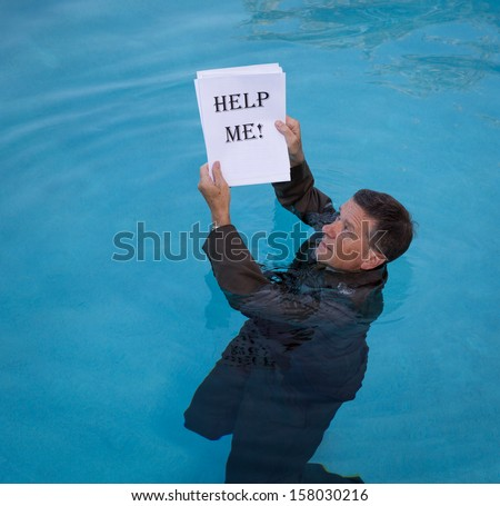 Senior caucasian businessman in suit up to neck in deep blue water worried about drowning in paperwork and holding help me document