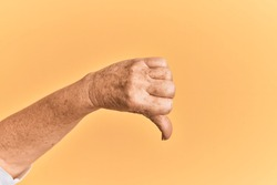 Senior caucasian hand over yellow isolated background doing thumbs down rejection gesture, disapproval dislike and negative sign