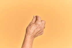 Senior caucasian hand over yellow isolated background holding blank space with thumb finger, business and advertising