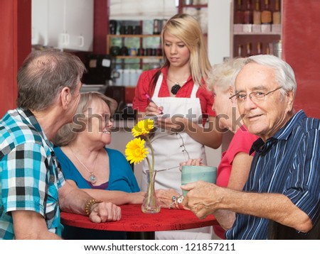 Senior Caucasian male sitting with friends in a cafe