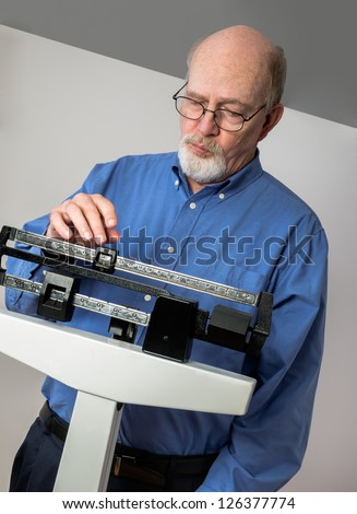 Senior caucasian man weighing himself on vertical weight scale. He looks thoughtful and concerned.