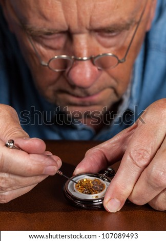 Senior caucasian repairman working on an old pocket watch