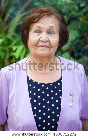 Senior Caucasian woman head and shoulders portrait against green leaves, looking at camera, one person