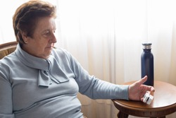 Senior caucasian woman over 70 using a pulse oximeter at home near a window