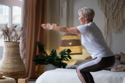 Senior caucasian woman practicing advanced yoga Chair Pose or Utkatasana at home