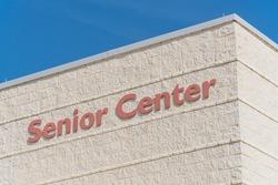 Senior center text close up on facade exterior building in Texas, America under sunny blue sky.