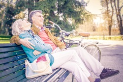 Senior cheerful couple sitting on a bench in a park - Two pensioners having fun together outdoors
