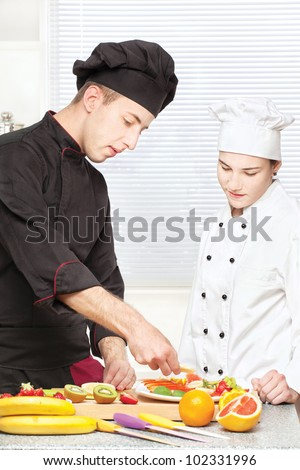 Senior chef teaches young chef to decorate fruit plate in kitchen