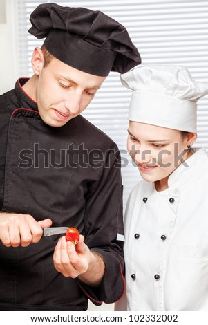Senior chef teaches young chef to decorate strawberry