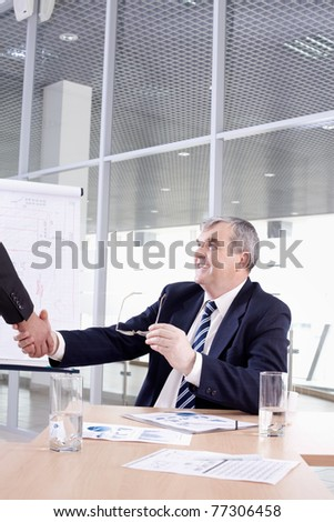 Senior chief shaking hands with his partner