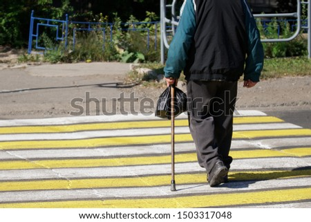 Senior citizen - an elderly man with a cane and a black bag crosses the road along a marked pedestrian crossing. Life in the city. Destroyed asphalt. Respect for old age. Daylight