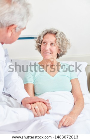Senior citizen as a patient in the hospital bed is cared for by her doctor